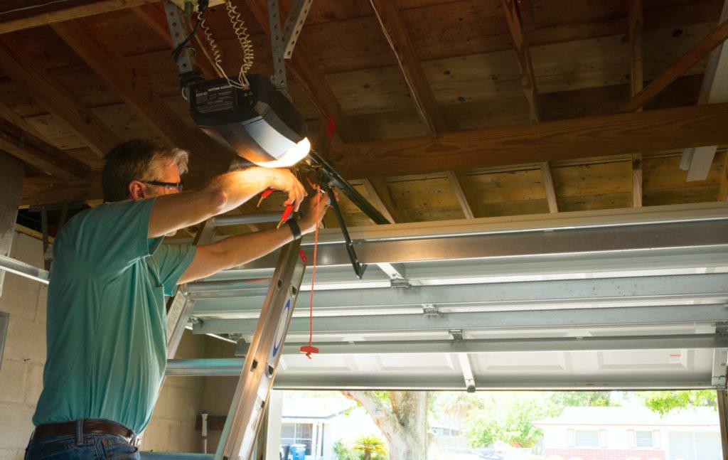 Man adjusting automatic garage door opener