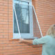 Woman removing window screen for cleaning wire screen on house window.