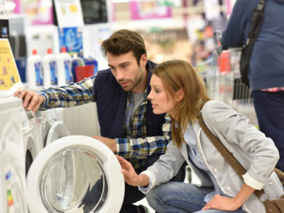 Young couple shopping for appliances, washer and dryer