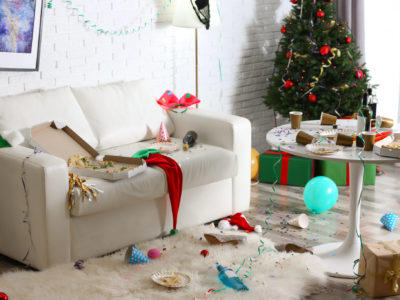 Messy living room interior with Christmas tree