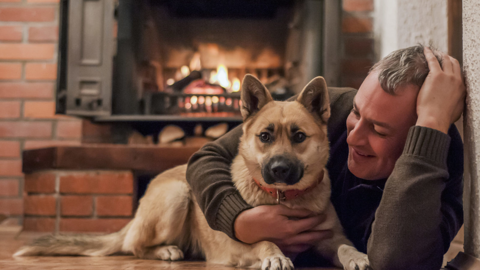 Man with dog and fireplace