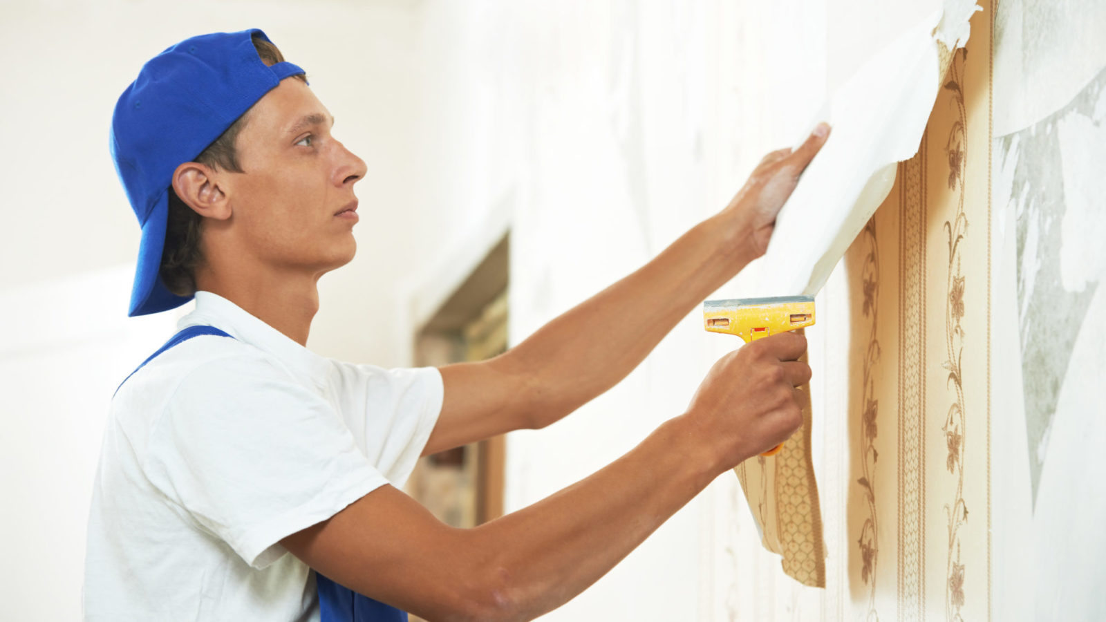 Homeowner peeling wallpaper from a wall