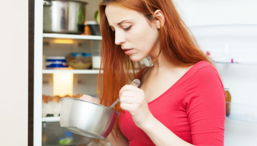 hungry girl in red eating from pan near fridge