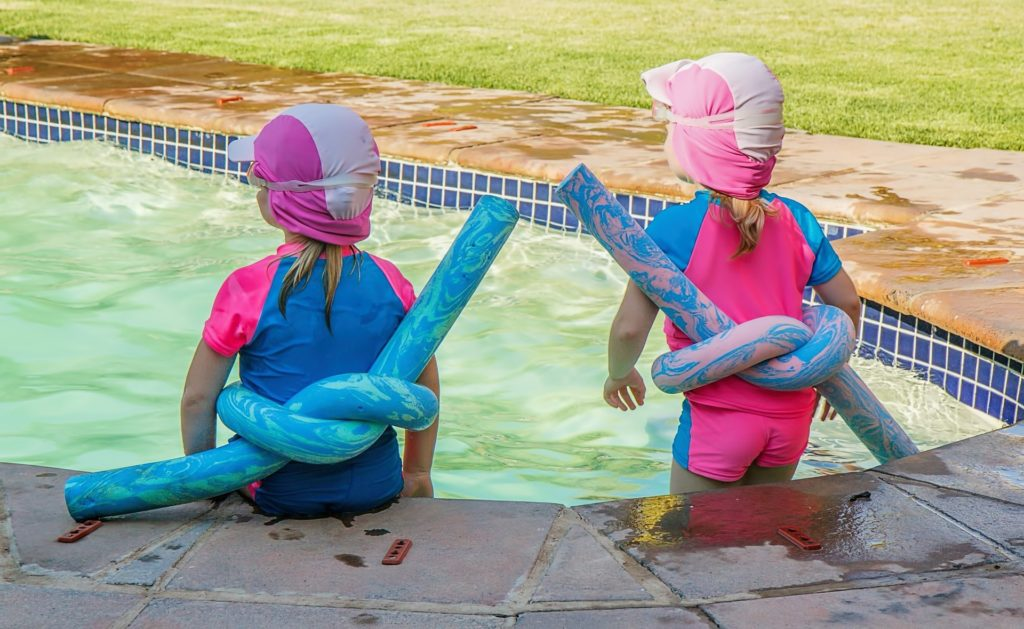 tw children sitting at the edge of a pool
