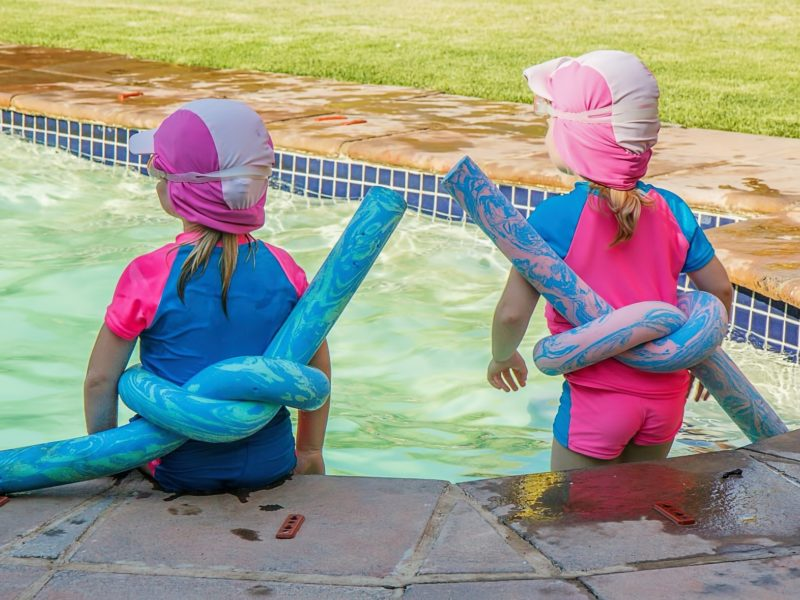 two children sitting at the edge of a pool