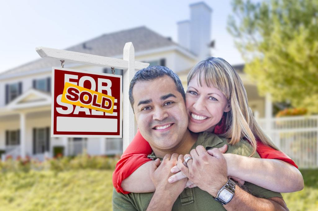 Home sellers happy in front of recently sold home