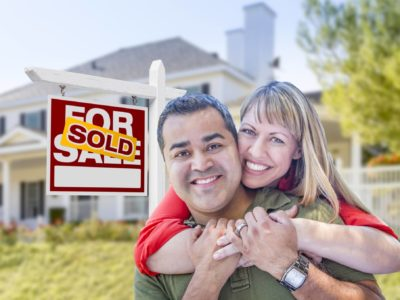 Couple hugging after buying a home