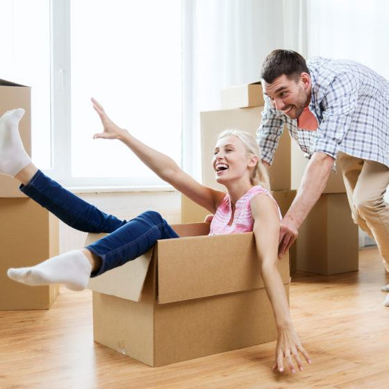 couple with cardboard boxes having fun at new home