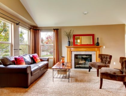 living_room_leather_couch__fireplace_decor_carpet_carpeting_windows_curtains__shutterstock_177044996