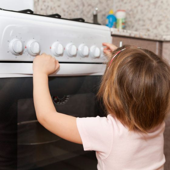 child  trying to turn on stove