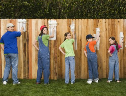 Family painting fence