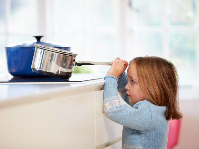 Child risking burn in kitchen