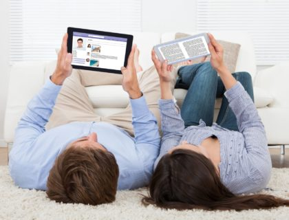 Couple Using Technologies At Home