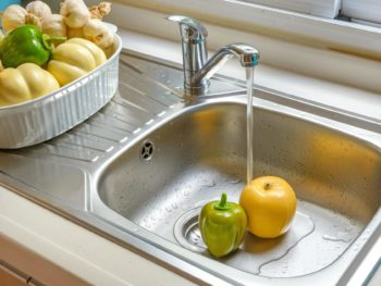 Kitchen faucet with flowing water washing vegetables
