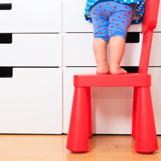 childproofing tips, kids safety concept- little girl climb on chair