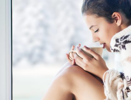 Young Woman Sipping Coffee in Winter