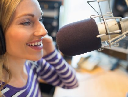 Happy young female radio host broadcasting in studio