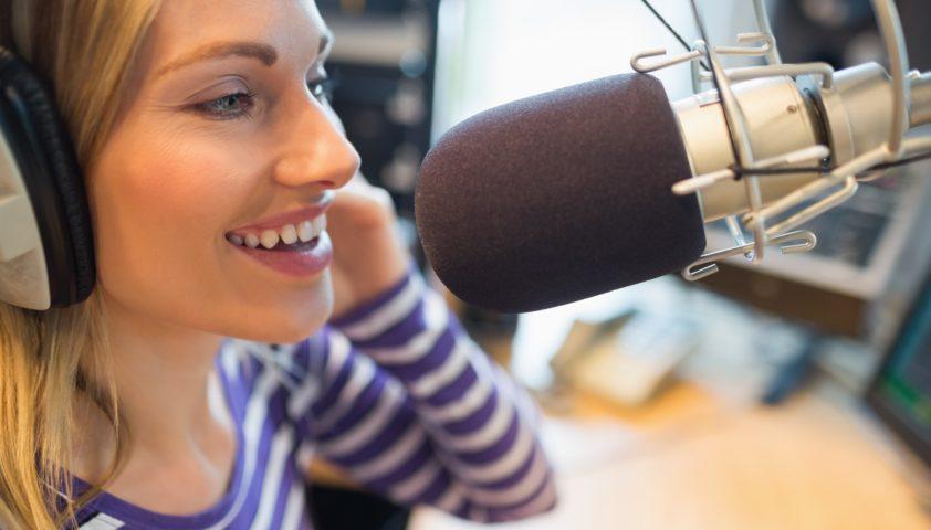 Happy young female radio host broadcasting in studio