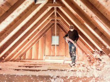 Man blowing insulation in an attic