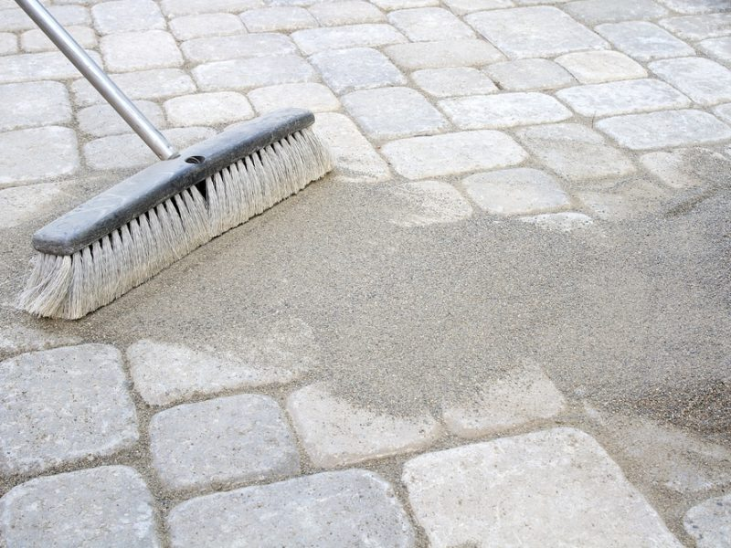 Sweeping sand on a paver brick patio