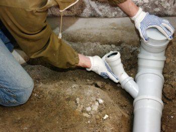 Man installs main plumbing drain pipe