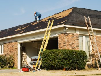 Workers replacing a roof on a house