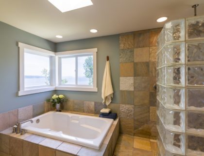 Contemporary upscale home spa bathroom interior with glass tile shower, slate tile walls, acrylic soaking tub, skylight and view windows