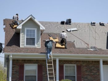 Workers replacing an older roof