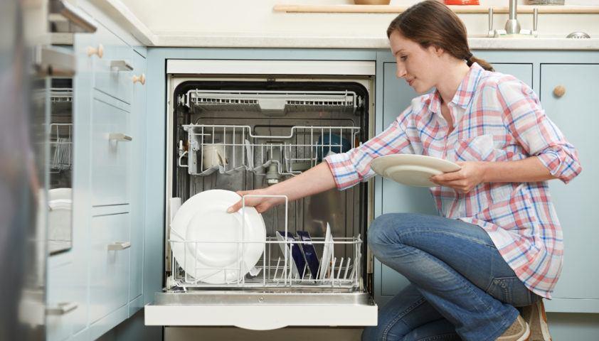 Woman Loading Dishwashwasher In Kitchen
