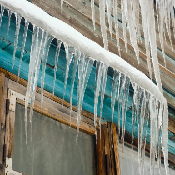 Long icicles hanging from the roof of  house.
