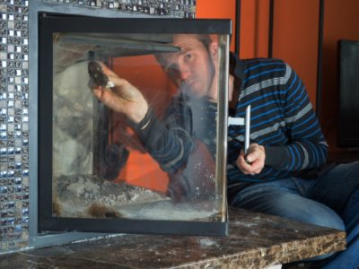 Man wipes the dirty glass of fireplace