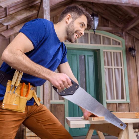 Man using a hand saw cutting wood