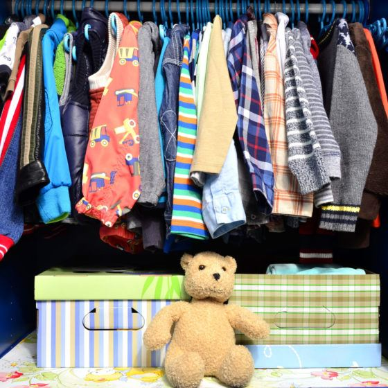 Dressing closet for kids with clothes arranged on hangers and teddy bears.Colorful wardrobe of newborn, toddlers, babies full of t-shirts,pants, shirts,blouses, onesie hanging,