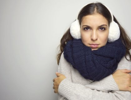 Shivering young woman being cold wearing earmuffs, sweater and scarf. Copy space.