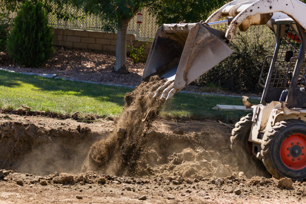 Small bulldozer digging In yard for a spool pool Installation