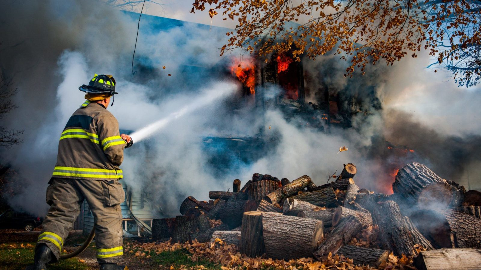 Firefighter at house with hose