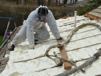 Technician applying spray foam insulation