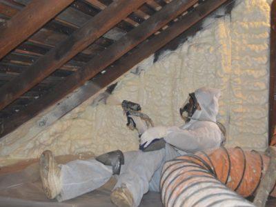 Man applying spray foam in attic