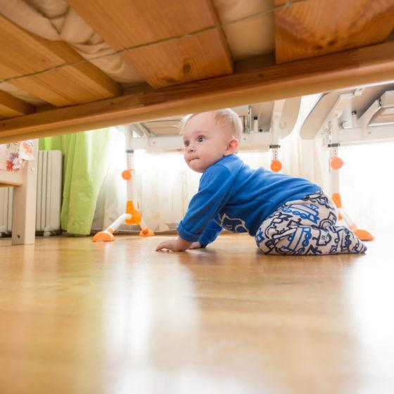 Baby boy crawling on floor and looking under the bed