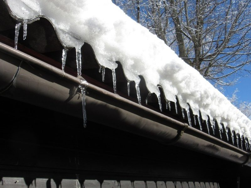 Ice dams on an old roof over a gutter
