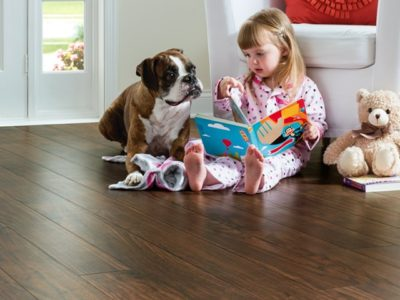 Child and dog sitting on EVP (engineered vinyl plank floor) which is durable and waterproof.
