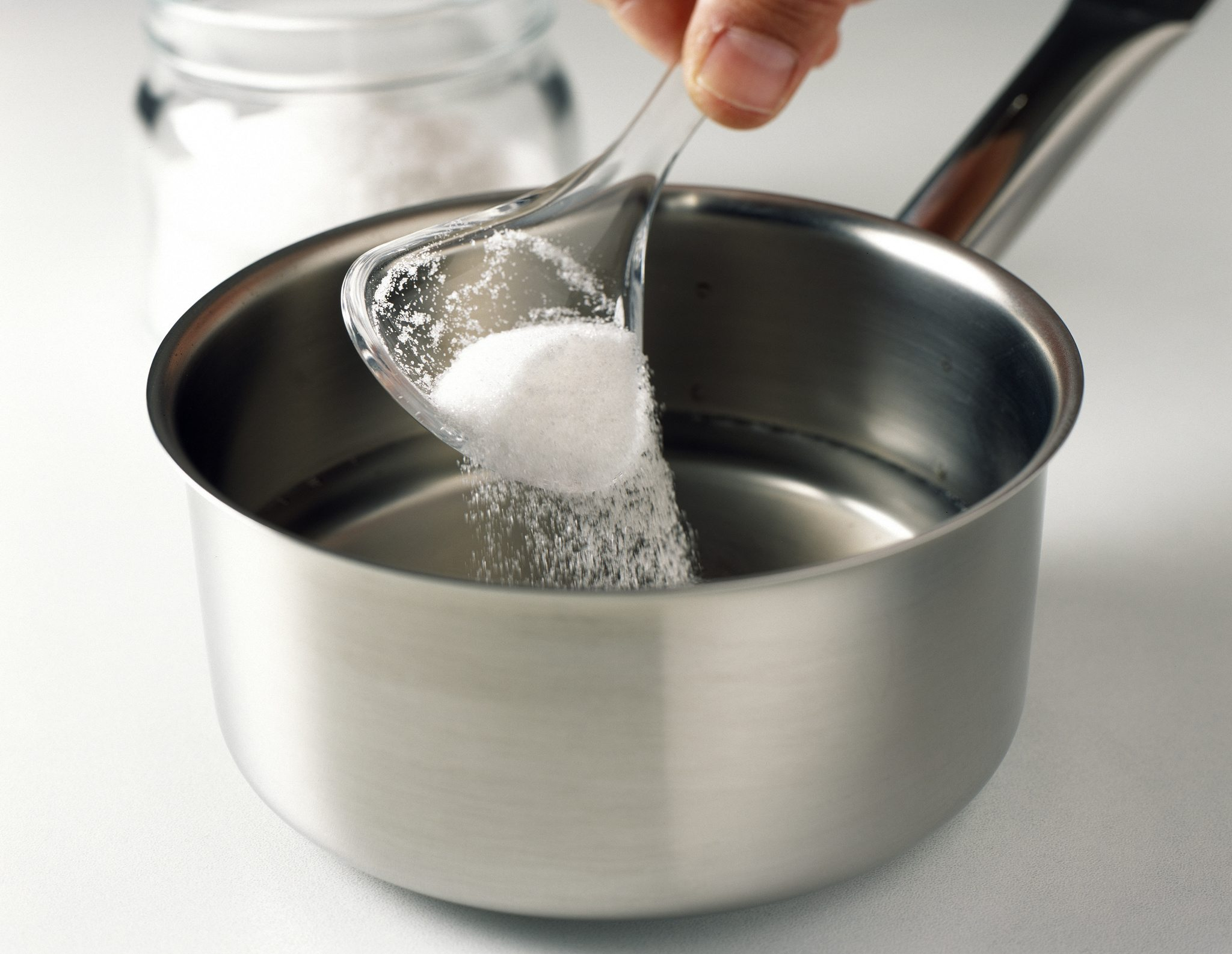 Sugar being poured into pot on stove