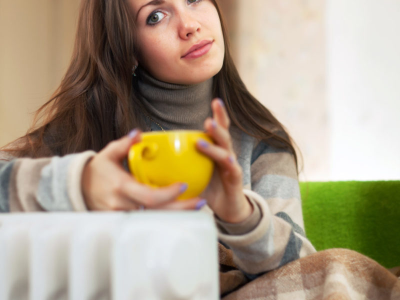woman with yellow cup near radiator at home