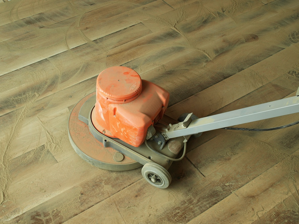 Using a floor buffer to sand and refinish a hardwood floor.