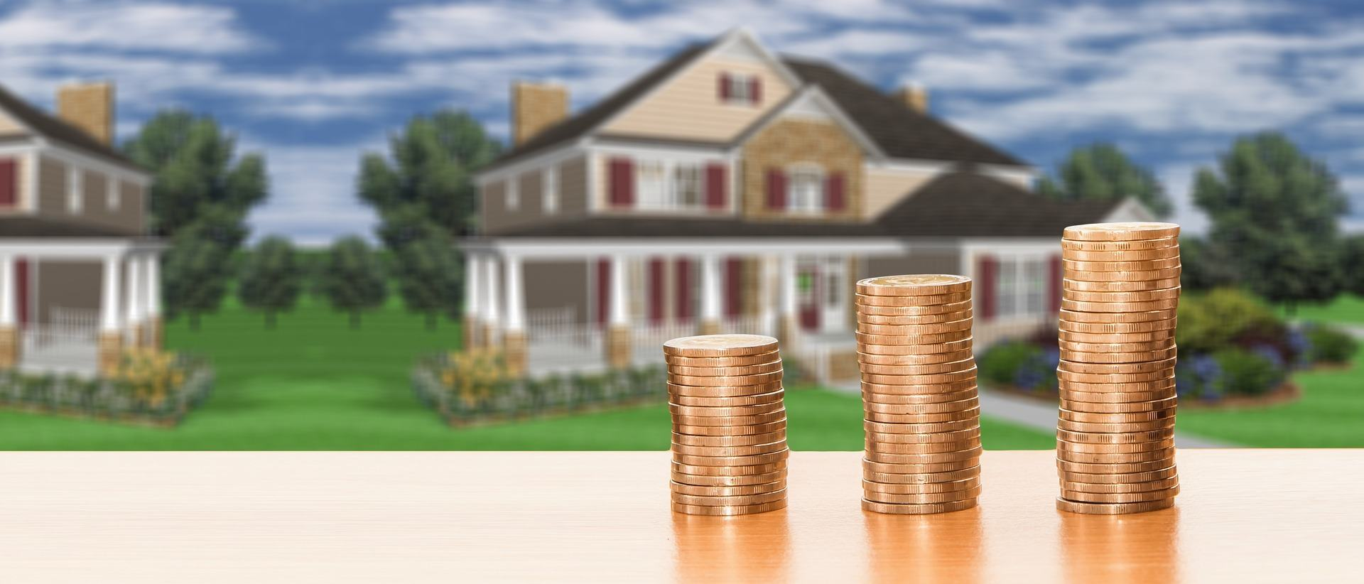 Money in front of a newly purchased home