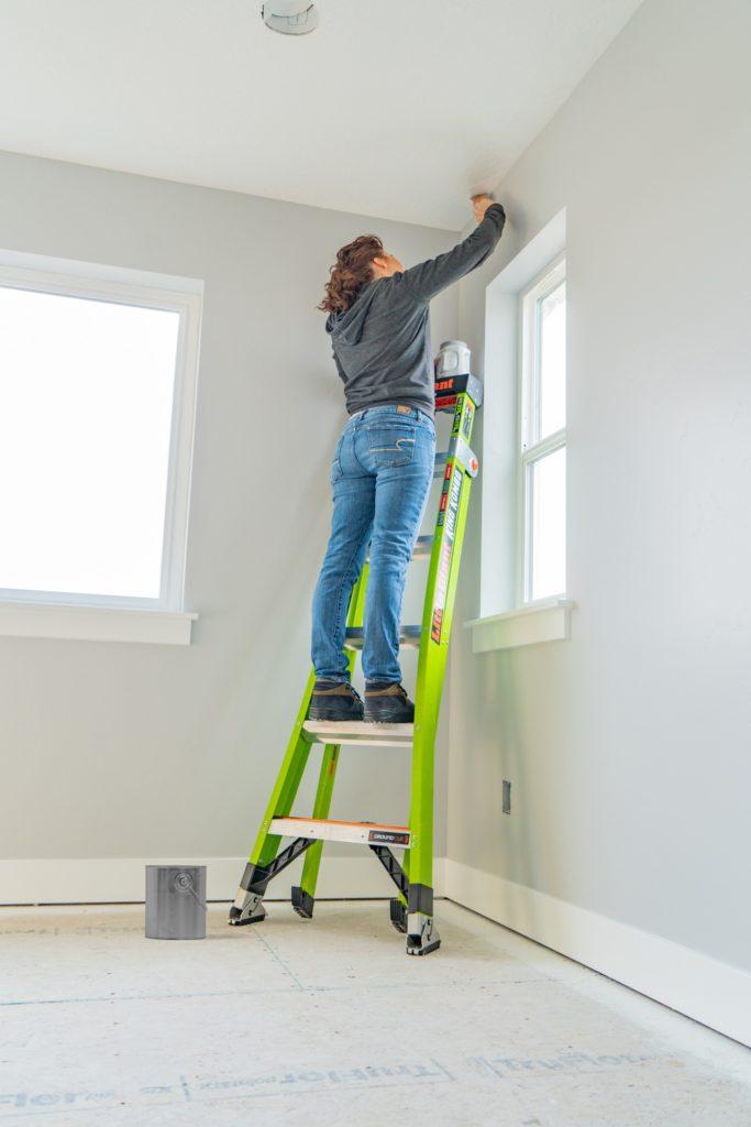Woman standing on Little Giant King Kombo ladder painting an inside wall corner.