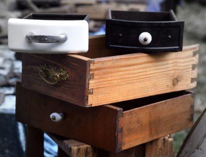 Vier verschiedene Schubladen gestapelt auf einem Flohmarktstand
