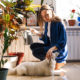 Young woman waters houseplants next to her dog