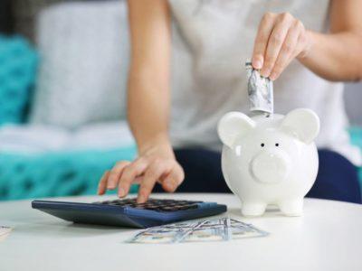 Millennial woman puts money in piggy bank