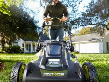 Man walking behind cordless lawn mower
